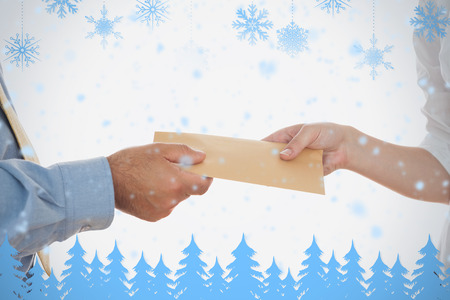Closeup of hands holding bribe against snowflakes and fir trees in blue photo