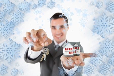 Close up of keys and miniature house being held by male estate agent against snowflake frame photo