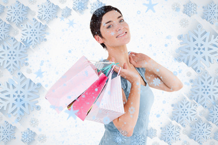 Darkhaired woman posing with shopping bags against snowflake frame photo
