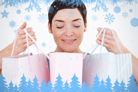 Woman looking at her shopping bags against snow flake frame in blue photo