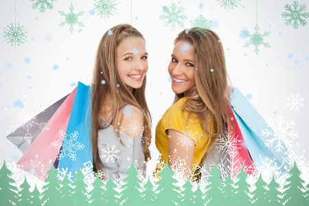 Two young women with shopping bags against snowflakes and fir trees in green photo