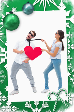 Brunette pulling her boyfriend by the tie against christmas frame photo