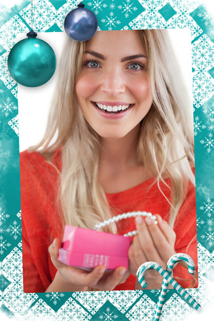 Cheerful woman discovering necklace in a gift box against christmas frame photo