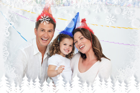 Portrait of cute little girl with her parents during a birthday against fir tree forest and snowflakes photo