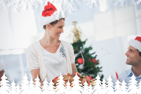 Cheerful woman wearing santa hat and bringing a roast chicken against fir tree forest and snowflakes photo