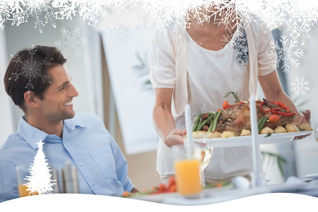 Smiling woman presenting a roast chicken during a dinner against fir tree forest and snowflakes photo