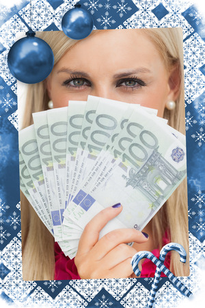 Green eyed woman holding 100 euros banknotes against christmas frame photo