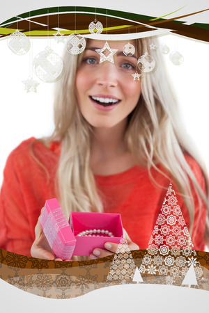 Surprised blonde woman opening gift against christmas frame photo