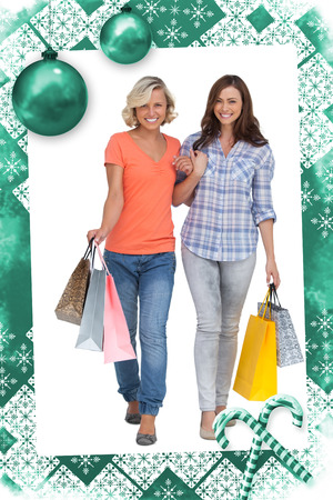 linking together: Two cheerful friends with shopping bags against christmas frame Stock Photo