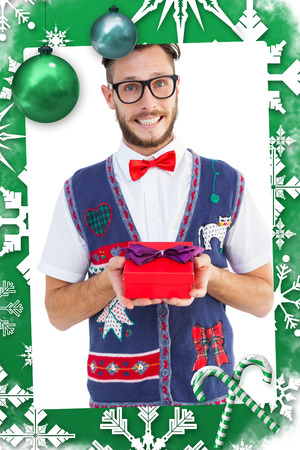 Geeky hipster offering christmas gift against christmas frame photo