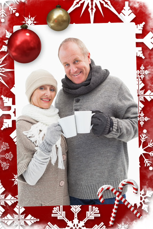 Happy mature couple in winter clothes holding mugs against christmas themed page photo