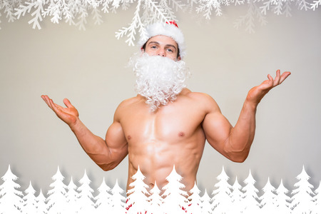 Portrait of shirtless macho man with fake santa beard against fir tree forest and snowflakes photo
