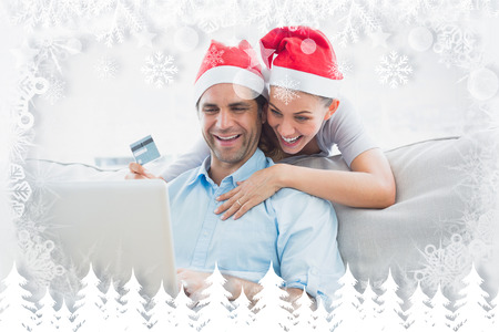 Smiling couple in santa hats shopping online with laptop against fir tree forest and snowflakes photo