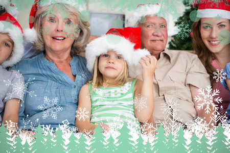 Happy multigeneration family wearing santa hats on the couch against snowflakes and fir trees in green photo