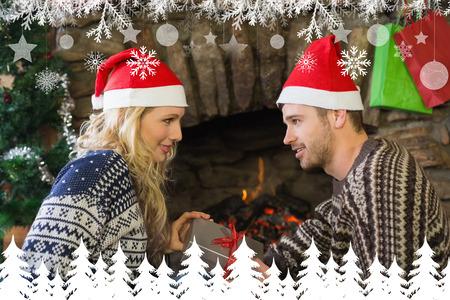 gifting: Gifting del hombre mujer frente a la chimenea encendida durante la Navidad contra abeto bosque �rbol y los copos de nieve