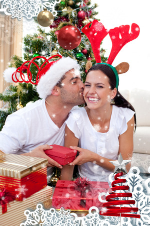Smiling couple giving presents for Christmas against snow falling photo