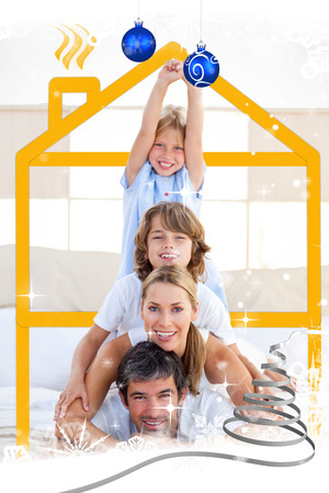 cuddling: Family having fun with yellow drawing house against snow falling