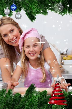 Mother and daughter baking Christmas cookies in the kitchen against snow falling photo