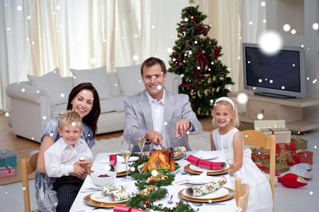 Family celebrating Christmas dinner with turkey against snow Stock Photo