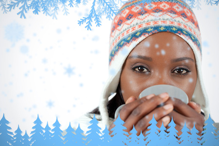 Student woman enjoying a cup of tea in the cold against frost and fir trees in blue photo