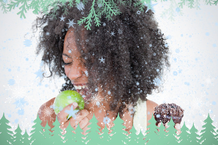 Young woman going to eat a delicious green apple against frost and fir trees in green photo