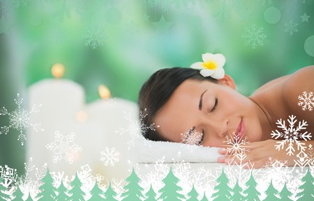 Beautiful brunette relaxing on massage table  against snowflakes and fir trees in green photo