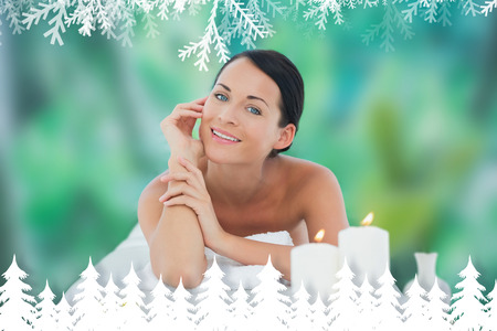 Beautiful brunette relaxing on massage table smiling at camera against fir tree forest and snowflakes photo