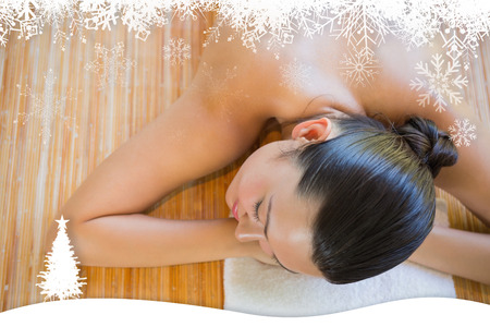 Content brunette relaxing on massage table against fir tree forest and snowflakes photo