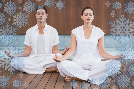 Attractive couple in white meditating in lotus pose against snowflake frame photo