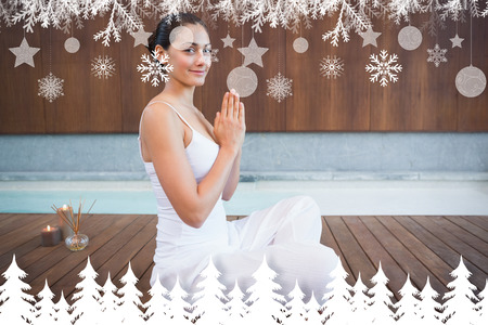 Content brunette in white sitting in lotus pose smiling at camera against fir tree forest and snowflakes photo