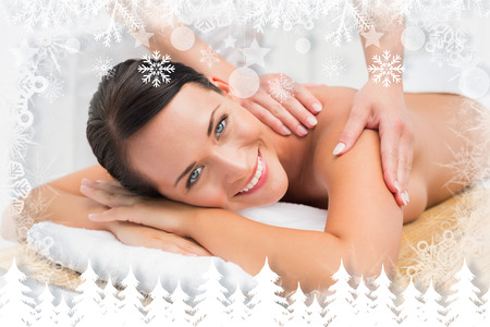 Beautiful brunette enjoying a shoulder massage smiling at camera against fir tree forest and snowflakes photo