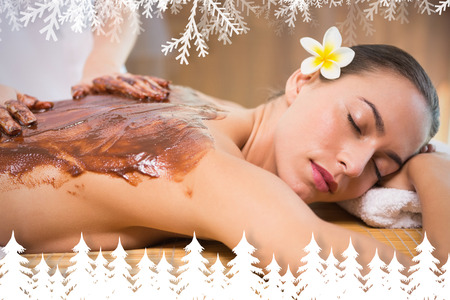 Attractive woman receiving chocolate back mask at spa center against fir tree forest and snowflakes photo