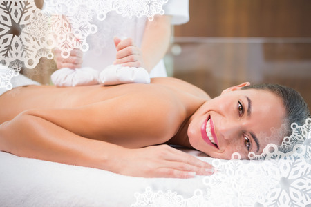 Attractive woman receiving treatment at spa center against snowflake frame photo