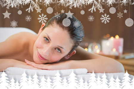 Beautiful woman lying on massage table at spa center against fir tree forest and snowflakes photo