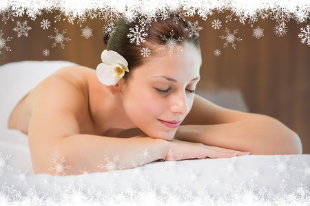 day care: Beautiful woman lying on massage table at spa center against fir tree forest and snowflakes
