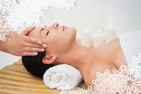 nieve navidad: Morena pac�fica disfrutando de un masaje facial contra el marco de copo de nieve Foto de archivo