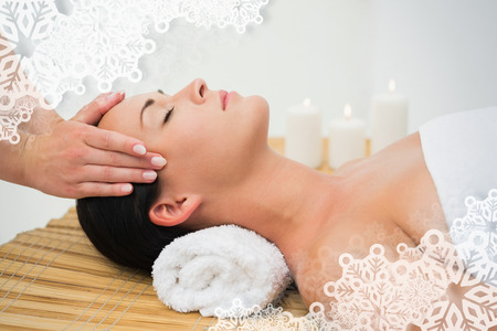 spa: Peaceful brunette enjoying a facial massage against snowflake frame