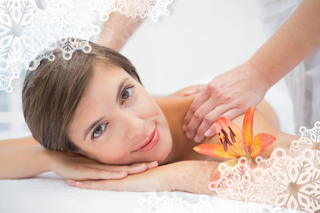 Attractive woman receiving shoulder massage at spa center against snowflake frame photo