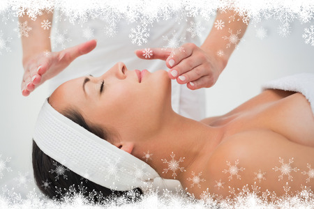Peaceful brunette getting reiki therapy against fir tree forest and snowflakes photo