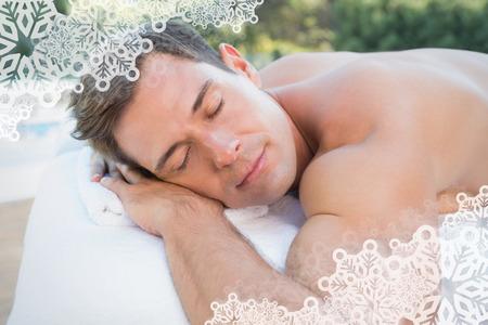 massage table: Peaceful man lying on massage table poolside against snowflake frame