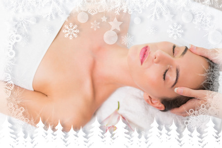 Attractive woman receiving head massage at spa center against fir tree forest and snowflakes