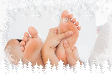 Close-up of a woman receiving foot massage against fir tree forest and snowflakes photo