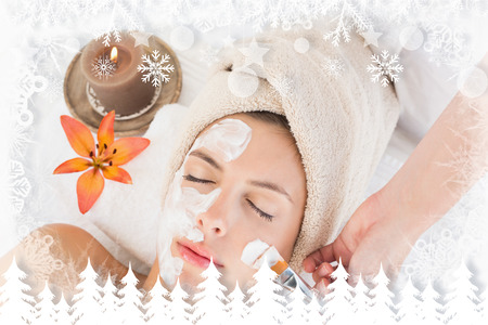 Attractive woman receiving treatment at spa center against fir tree forest and snowflakes photo