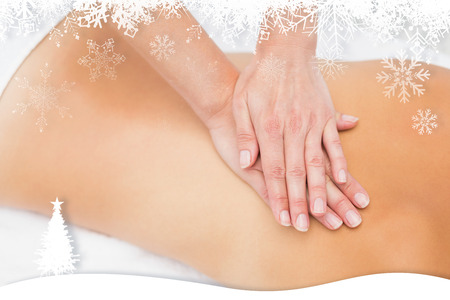 Woman receiving back massage at spa center against fir tree forest and snowflakes photo