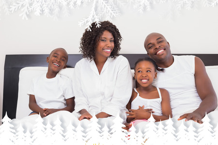 Happy family having breakfast in bed against fir tree forest and snowflakes photo
