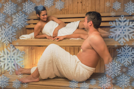 Calm couple relaxing in a sauna and chatting against snowflake frame photo