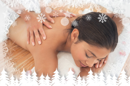 therapy room: Beautiful brunette enjoying a back massage  against fir tree forest and snowflakes