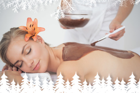 beauty treatment: Beautiful blonde enjoying a chocolate beauty treatment  against fir tree forest and snowflakes