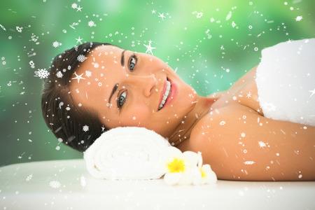 snow falling: Bella bruna rilassante sul lettino da massaggio sorridente a porte chiuse contro la neve caduta Archivio Fotografico