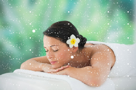 Beautiful brunette relaxing on massage table against snow falling photo